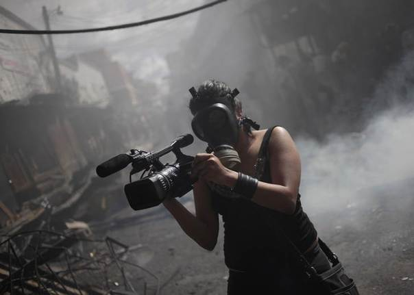 A member of the local media records a fire at the Comayaguela market in Tegucigalpa February 18, 2012. REUTERS/Jorge Dan Lopez