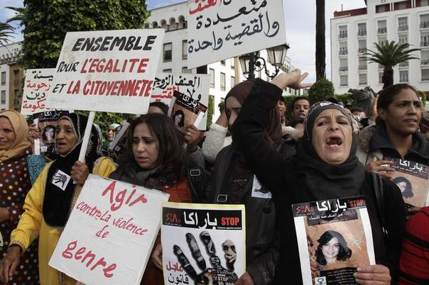Women from different regions of Morocco hold placards with slogans such as