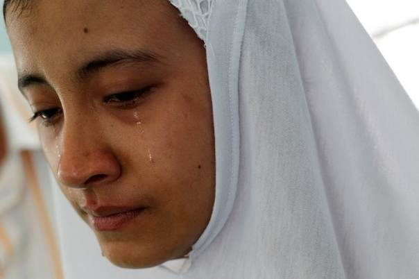 A relative cries near the body of her uncle, a 51-year-old man who was killed in a recent riot, at a mosque in Mandalay July 3, 2014. REUTERS/Soe Zeya Tun