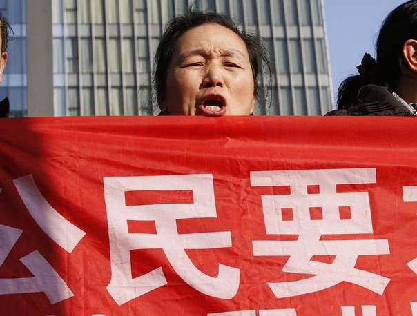 Supporters of Xu Zhiyong, one of China's most prominent rights advocates, shout slogans near a court where Xu's trial is being held in Beijing. The slogan on the placard is a part of slogan that reads: