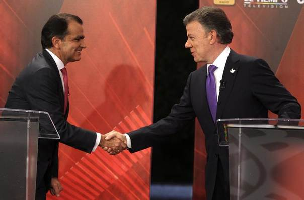 Colombia's President and presidential candidate Juan Manuel Santos (R) shakes hands with presidential candidate Oscar Ivan Zuluaga during a television debate in Bogota June 9, 2014 REUTERS/John Vizcaino