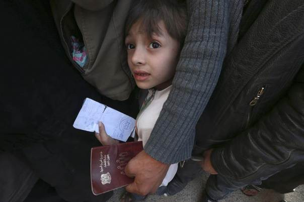 A boy carries identification papers while waiting to receive humanitarian aid in Duma, Damascus, March 29, 2014. Picture taken March 29, 2014. REUTERS/Bassam Khabieh