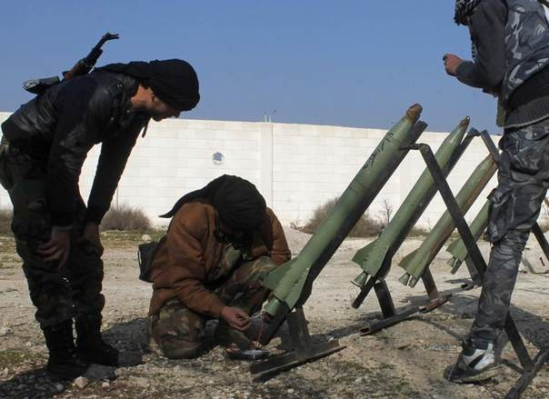 Fighters from the Free Syrian Army's Saif al-Umayyad brigade prepare rockets to be launched towards forces loyal to Syria's President Bashar al-Assad in the eastern Damascus suburb of Ghouta January 16, 2014. REUTERS/Rafat Beram