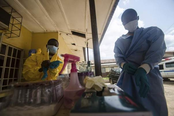 Medical staff put on protective gear in Kenema government hospital before taking a sample from a suspected Ebola patient in Kenema, Sierra Leone, July 10, 2014. REUTERS/Tommy Trenchard