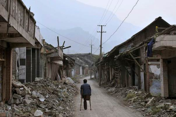A man who lost a leg in the 2008 Sichuan earthquake makes his way home amidst the ruins in Sichuan province, China, on April 16, 2009. REUTERS/Stringer