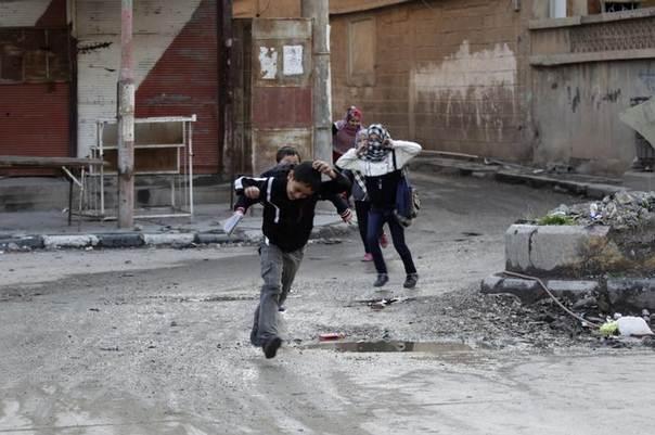 Children run across a street to avoid snipers in Deir al-Zor, eastern Syria, February 16, 2014. REUTERS/Khalil Ashawi