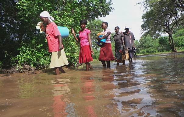 Women and girls negotiate their way along a flooded road to a safety point in Gombera village, Muzarabani, Zimbabwe. TRF/Jeffrey Gogo