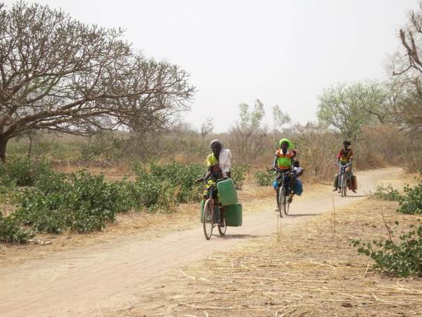 Women cycle with water tins towards the village of Bagare, Passore province, northern Burkina Faso, March 30, 2016 REUTERS/Zoe Tabary