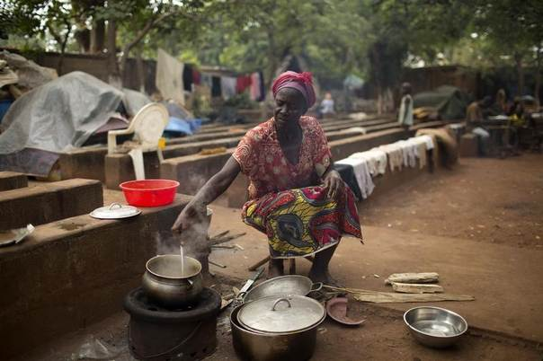 Kapiri Agnes prepares a meal in the grounds of a church that is sheltering about 4000 internally displaced persons who have fled sectarian violence in Bangui, March 13, 2014. REUTERS/Siegfried Modola