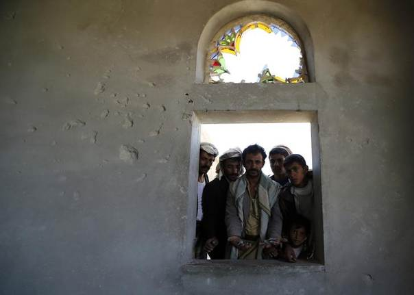 People look from the window of a house damaged during recent fighting between Shi'ite Muslim rebels and government forces near the northwestern Yemeni city of Omran June 9, 2014. REUTERS/Khaled Abdullah