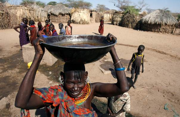 A Turkana woman carries water on her head before attending a drought and peace meeting in Lobei village of Turkana district in northwest Kenya, October 2, 2009. REUTERS/Thomas Mukoya