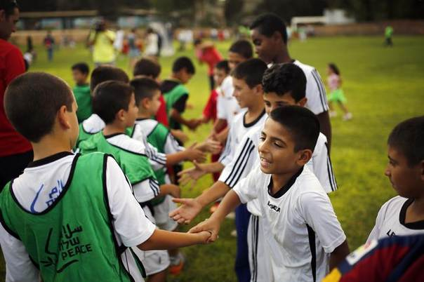 Israeli and Palestinian children shake hands during an event opening a year of training of an Israeli-Palestinian soccer program launched by the Peres Center for Peace, in Kibbutz Dorot, outside the Gaza Strip, September 1, 2014. REUTERS/Amir Cohen