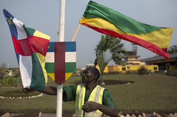 A man fixes flags of the Central African Republic (L) and Congo Brazzaville prior to the arrival of visiting heads of state on the day of the swearing-in ceremony of the new parliamentary-elected interim President Catherine Samba-Panza, at the airport of the capital Bangui, CAR, January 23, 2014. REUTERS/Siegfried Modola