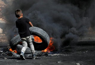 A Palestinian boy puts a tyre on fire during clashes with Israeli troops near the Jewish settlement of Qadomem, in the West Bank village of Kofr Qadom, near Nablus