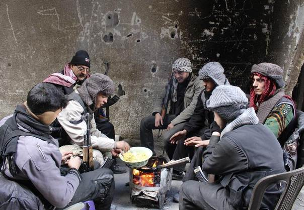 Free Syrian Army fighters sit around a fire in the eastern Damascus suburb of Ghouta, Syria, January 9, 2014. REUTERS/Ammar Al-Erbeeni