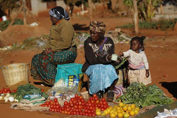 Vegetable vendors wait for customers at a market outside Harare August 1, 2013. REUTERS/Siphiwe Sibeko