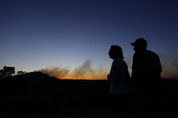 Kim Clements and Jerry Clements are silhouetted as they watch smoke rise from the Doce Fire in Yavapai County, Arizona, June 19, 2013. REUTERS/Joshua Lott