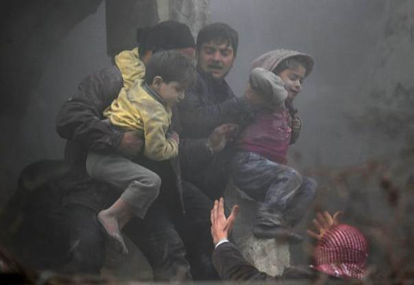 Men help wounded children who survived what activists say was an airstrike by forces loyal to Syrian President Bashar al-Assad in the Duma neighbourhood of Damascus January 7, 2014. REUTERS/Bassam Khabieh