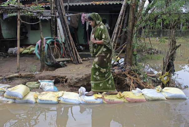A woman walks over sandbags on a flooded road in Khurda district in the eastern Indian state of Odisha, Oct. 27, 2013. REUTERS/Stringer