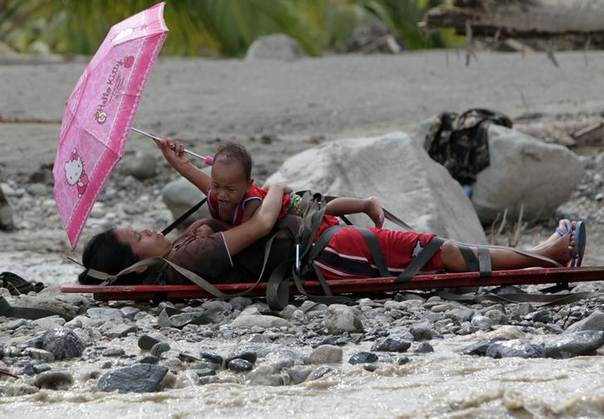 A six-months pregnant woman who survived flooding holds her child on a stretcher while waiting to be evacuated in New Bataan town, Compostela Valley, southern Philippines December 6, 2012.  REUTERS/Erik De Castro
