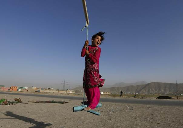 A girl plays on a whirl during Eid al-Fitr in Kabul July 28, 2014. REUTERS/Mohammad Ismail