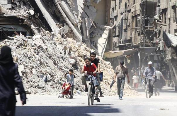 Boys ride a bicycle past other civilians near damaged buildings in the Damascus suburb of Harasta August 24, 2014. Picture taken August 24, 2014. REUTERS/Badra Mamet