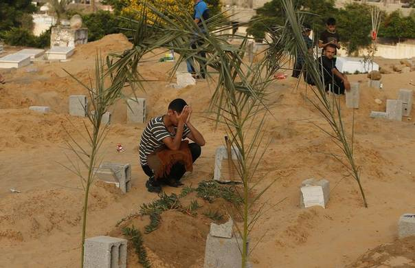 A Palestinian boy mourns next to his brother's grave, who medics said was killed during the Israeli offensive, during the Muslim holiday of Eid al-Fitr at a cemetery in Beit Lahiyah in the northern Gaza Strip, July 28, 2014. REUTERS/Suhaib Salem