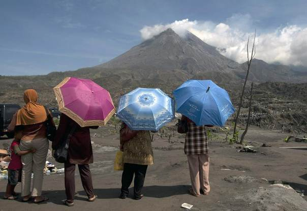 Indonesians look at the devastation caused by Mount Merapi volcano (in the background) in Kinahrejo village, in Yogyakarta Dec. 14, 2010. REUTERS/Dwi Oblo