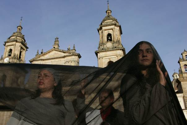 In a 2009 file photo, demonstrators protesting against violence in Colombia, perform during a rally entitled