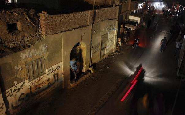 People and vehicles are seen during a power cut in Toukh, El-Kalubia governorate, about 25 km (16 miles) northeast of Cairo, Egypt, May 26, 2013. REUTERS/Amr Abdallah Dalsh