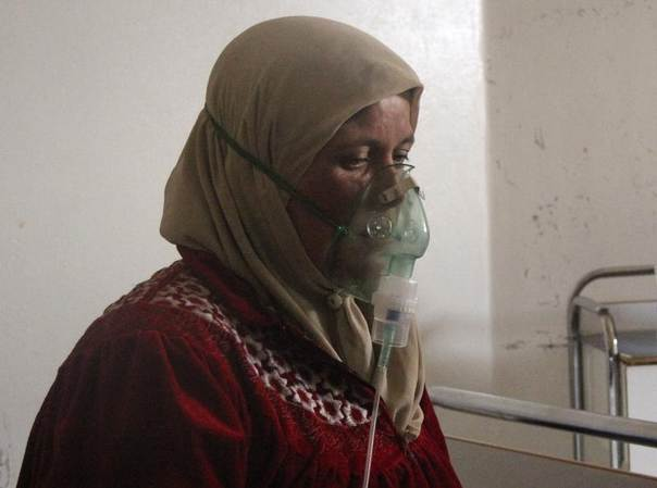 A woman, affected by what activists say was a gas attack, breathes through an oxygen mask inside a field hospital in Kfar Zeita village in the central province of Hama, Syria, April 12, 2014. REUTERS/Stringer
