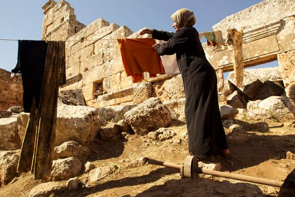 A Syrian woman hangs clothes to dry while taking shelter inside ruins she fled to in fear of shelling near Idlib on October 16, 2013. REUTERS/Loubna Mrie