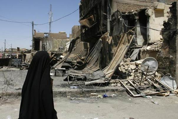 A woman walks past market stalls destroyed during Tuesday's bomb attack in Baghdad's Hurriya district June 20, 2008. REUTERS/Omar Obeidi