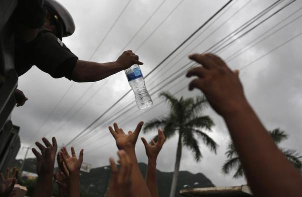 A soldier hands out bottled water to residents in Acapulco September 18, 2013. REUTERS/Tomas Bravo