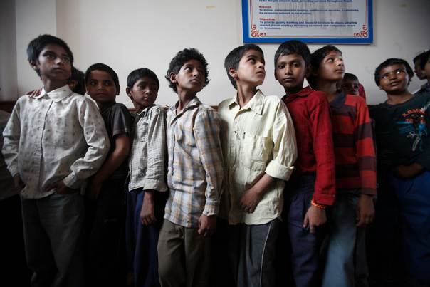 Trafficked children, mostly under the age of 14, queue for medical examination after being rescued from a sari embroidery factory near Kathmandu on July 4, 2012. REUTERS/Navesh Chitrakar