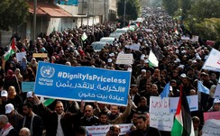 A Palestinian employee of the United Nations Relief and Works Agency (UNRWA) holds a sign during a protest against a U.S. decision to cut aid, in Gaza City January 29, 2018