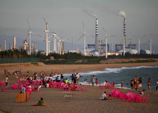 Windmills and a power plant are seen in the distance as beachgoers watch sunset in the city of Dongfang on the west side of China's island province of Hainan, June 18, 2014. REUTERS/John Ruwitch