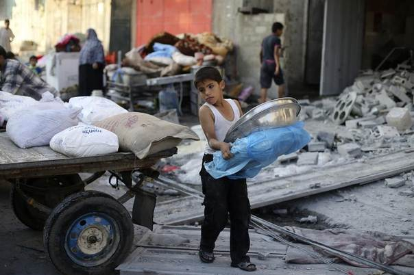 A Palestinian boy carries belongings near his family's damaged house, which witnesses said was hit by an Israeli air strike, in Rafah in the southern Gaza Strip August 26, 2014. REUTERS/Ibraheem Abu Mustafa