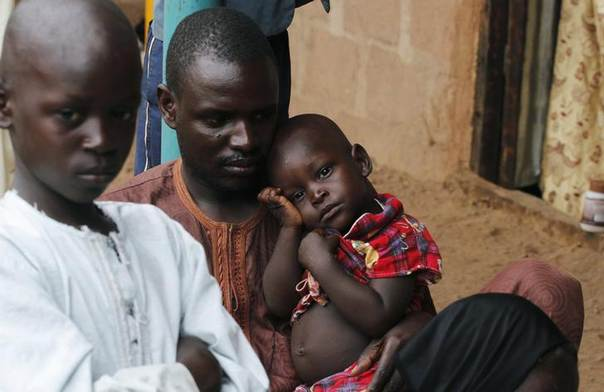 A man holds a boy as another looks on at the internally displaced persons (IDP) camp for those fleeing violence from Boko Haram insurgents at Wurojuli, Gombe State September 2, 2014. REUTERS/Samuel Ini