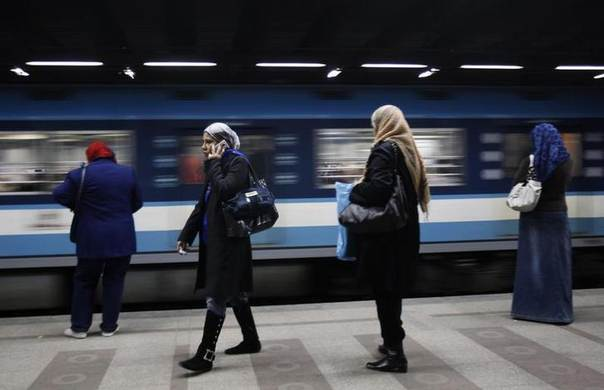 A woman speaks on the phone at a metro station in Cairo February 14, 2011. REUTERS/Asmaa Waguih