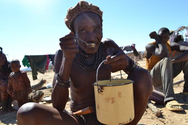 A Himba man eats maize meal in Opuwo, Kunene, northern Namibia. Drought across Namibia means 14 percent of the population need immediate food aid, and malnutrition is worsening in children. Kunene is one of the worst hit areas. Photo by Hanna Butler, IFRC, June 2013