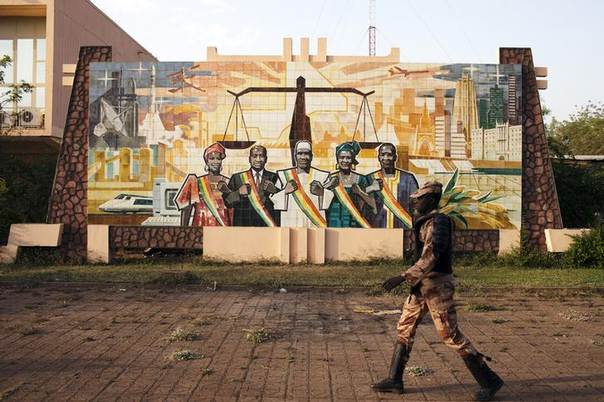 A gendarme walks past a mural outside the parliament building in Bamako February 19, 2014 REUTERS/Joe Penney
