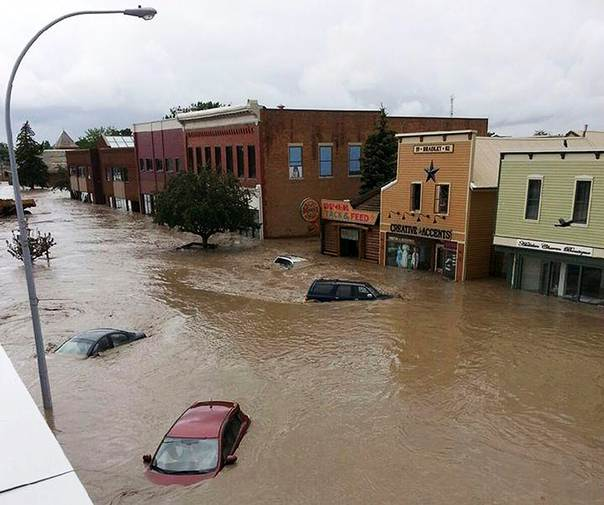 Cars float in water covering a downtown street in High River, in Canada's province of Alberta, on June 20, 2013. REUTERS/Stringer