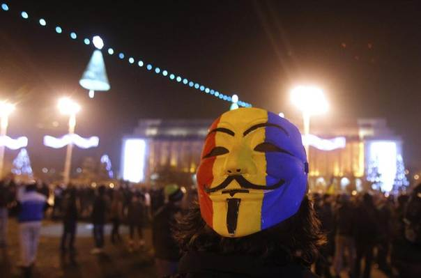 A man wearing a Guy Fawkes mask painted in Romanian national flag's colours attends a protest in front of Victoria palace, Romania's government headquarters, in Bucharest December 21, 2013 REUTERS/Bogdan Cristel