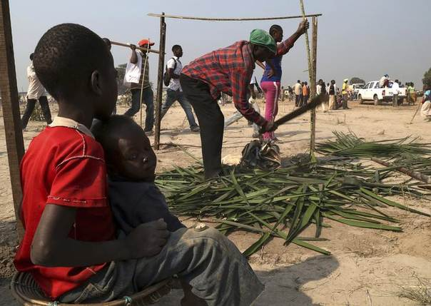 Newly arrived displaced refugees build a makeshift hut at the airport camp outside the capital Bangui January 7, 2014. REUTERS/Emmanuel Braun