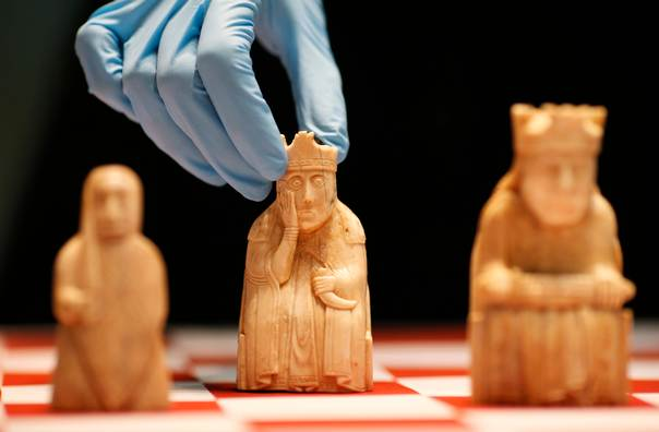 A worker at the British Museum arranges the Lewis Chessmen on a chess board in London on March 16, 2009. REUTERS/Andrew Winning