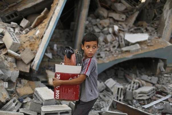 A Palestinian boy carries belongings as he walks past a house which police said was destroyed in an Israeli air strike, in Gaza City July 21, 2014 REUTERS/Suhaib Salem