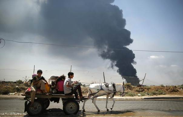 Palestinians ride a donkey cart as smoke rises from Gaza's main power plant, which witnesses said was hit in Israeli shelling, in the central Gaza Strip July 29, 2014. REUTERS/Mohammed Salem