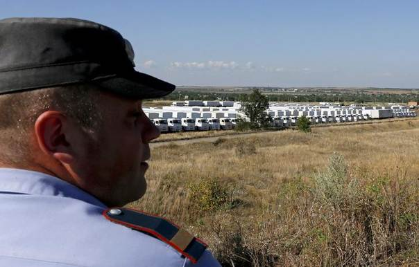 A Russian convoy of trucks carrying humanitarian aid for Ukraine is parked at a camp, with an Interior Ministry member seen in the foreground, near Kamensk-Shakhtinsky, Rostov Region, August 21, 2014.  REUTERS/Alexander Demianchuk