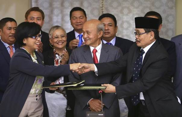 Government of the Philippines (GPH) chief negotiator Miriam Coronel Ferer shake hands with Moro Islamic Liberation Front (MILF) chief negotiator Mohagher Iqbal (R), exchanging peace agreements between both parties at the GPH-MILF Formal Exploratory Talk in Kuala Lumpur January 25, 2014. REUTERS/Samsul Said